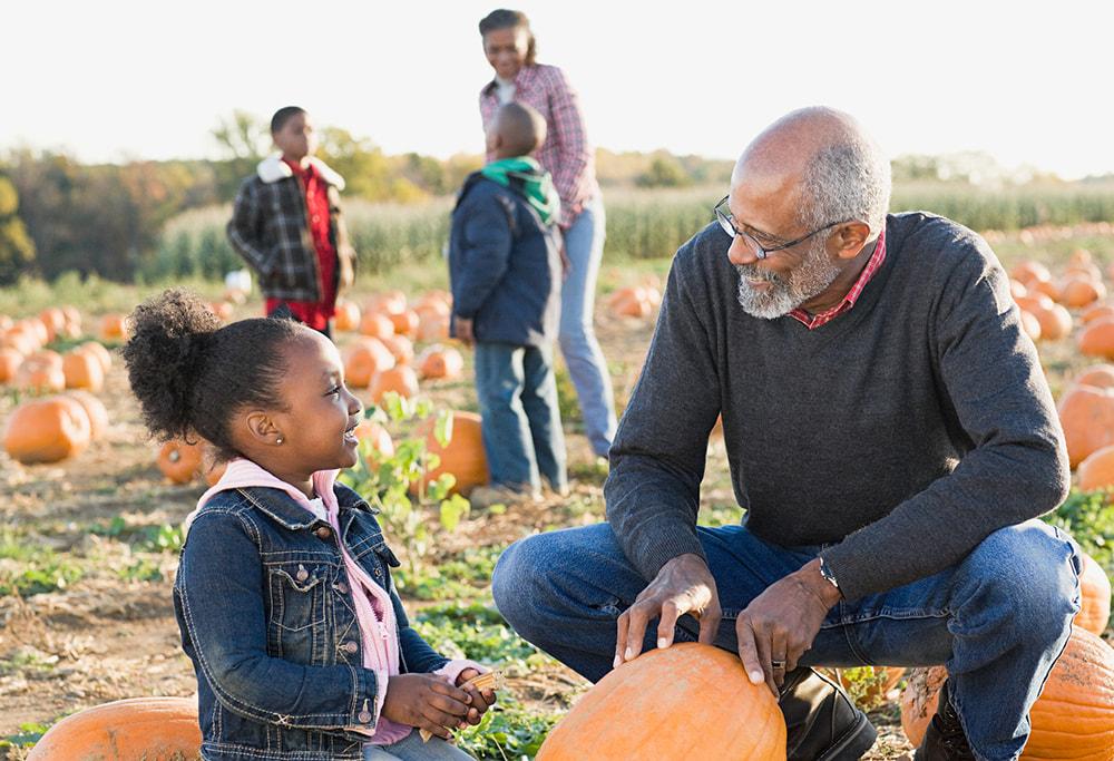 senior man picking pumpkin with grandchild